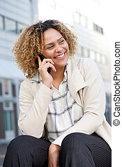 cheerful young african american woman talking on mobile phone in city