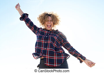 cheerful young African american woman with arm raised outside
