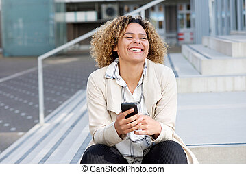 cheerful young african american woman with mobile phone outside