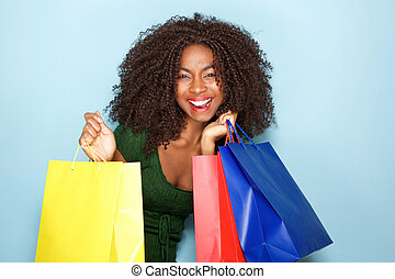 cheerful young african woman with shopping bags on blue background