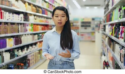 Portrait of cheerful young Asian woman behind counter ...