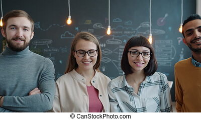 Portrait of cheerful young colleagues standing in cozy creative office smiling