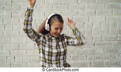 Portrait of cheerful young lady dancing and singing listening to radio in wireless headphones wearing trendy female shirt. Modern technology, culture and people concept.