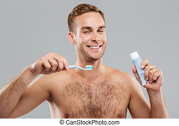 Portrait of cheerful young man with toothbrush and...