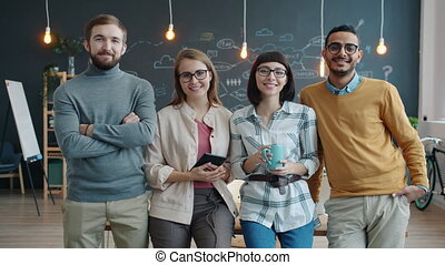 Portrait of cheerful young people coworkers standing in creative shared office smiling