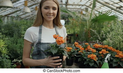 Portrait of Cheerful young woman garden worker in apron...