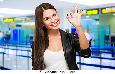 Portrait Of Cheerful Young Woman Gesturing Okay Sign at an aiport