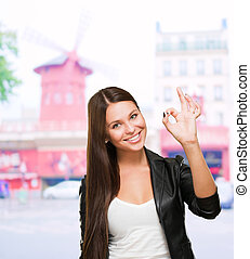 Portrait Of Cheerful Young Woman Gesturing Okay Sign