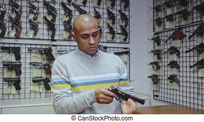 Portrait of cheerful young woman having fun in gun shop, imitating aiming with two handguns. High quality FullHD footage