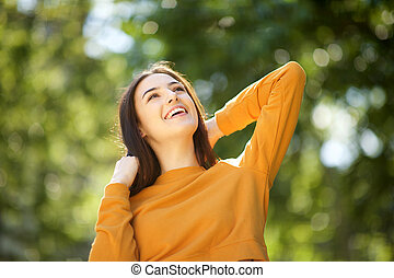 cheerful young woman in park with hands in hair