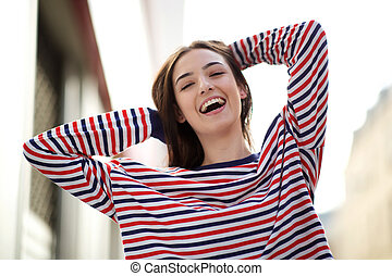 cheerful young woman laughing with hand in hair outside