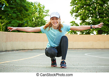 Portrait of cheerful young woman ready to start running session.