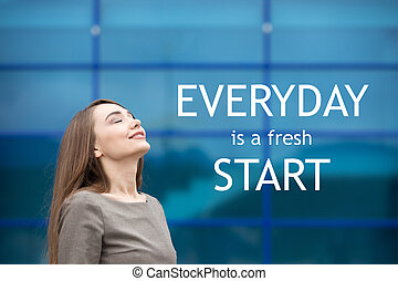 "Portrait of cheerful young woman relaxing outdoors with closed eyes. Happy beautiful successful female breathing fresh air on the street in summer. Motivational text ""Everyday is a fresh start"""