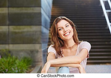 cheerful young woman sitting outdoors and smiling