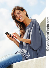 cheerful young woman sitting outside with mobile phone