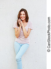 cheerful young woman smiling against white wall