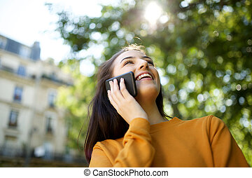cheerful young woman talking with mobile phone in park