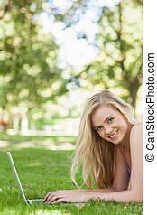 Portrait of cheerful young woman using her notebook lying on a lawn smiling at camera