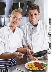 Portrait Of Chef Instructing Female Trainee In Restaurant Kitchen