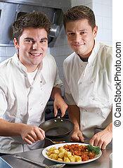 Portrait Of Chef Instructing Trainee In Restaurant Kitchen