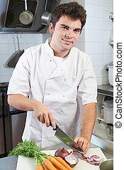 Portrait Of Chef Preparing Vegetables In Restaurant Kitchen