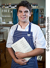 Portrait Of Chef Standing In Restaurant Holding Menu