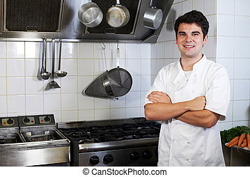 Portrait Of Chef Wearing Whites Standing By Cooker In Kitchen