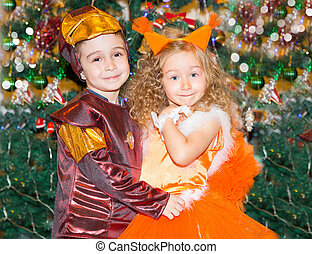 Portrait of child girl and boy in a suit squirrels around a Christmas tree decorated. Kids on holiday new year