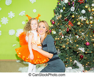 Portrait of child girl in a suit squirrels with mother around a Christmas tree decorated. Kid on holiday new year