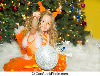 Portrait of child girl in a suit squirrels around a Christmas tree decorated. Kid on holiday new year