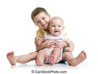 Portrait of child hugging his little cute sister sitting on floor isolated on white background