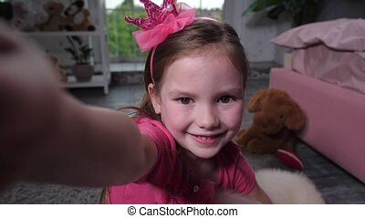 Portrait of child taking selfie with puppy at home -...