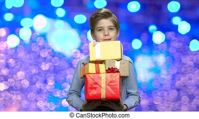 Portrait of child with Christmas gift boxes. Cute little boy...