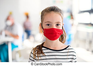 Portrait of small child with face mask, coronavirus, covid-19 and vaccination concept.