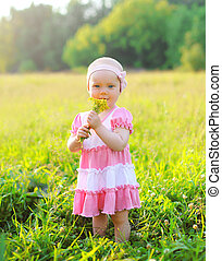 Portrait of child with flowers on the grass in summer day