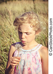 portrait of child with giant dandelion flower
