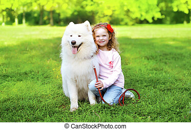 Portrait of child with white Samoyed dog on the grass in sunny summer day
