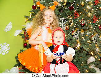 Portrait of children girls in a suit squirrels around a Christmas tree decorated. Kids on holiday new year