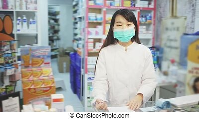 Chinese woman pharmacist in protective facial mask keeps track of drugs in interior of pharmacy