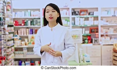 Portrait of chinese female pharmacist in modern pharmacy. High quality FullHD footage