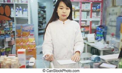 Happy chinese female pharmacist demonstrating assortment of pharmacy