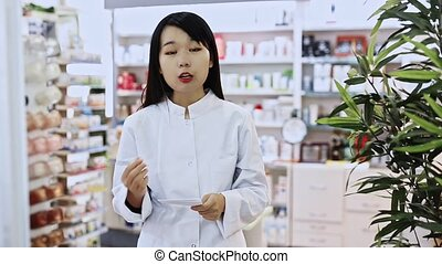 Portrait of chinese female pharmacist is standing with ...