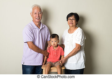 Portrait Of Chinese Grandparents With Grandson  At Home Together