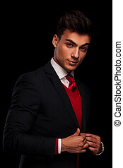 portrait of classy young man in suit, fixing his jacket while looking at the camera in dark studio background