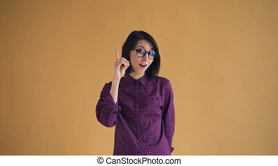 Portrait of clever woman in glasses having good idea raising...