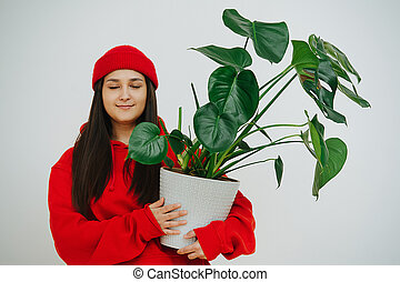 close eyes girl in red holding a pot with a home plant monstera