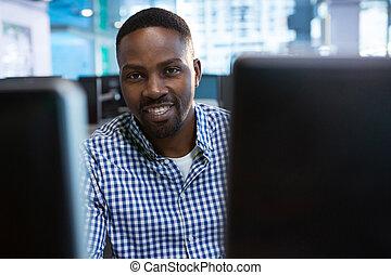 Portrait of computer engineer sitting at desk