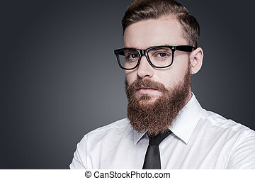 Portrait of confidence and creativity. Handsome young bearded man in shirt and tie looking at camera while standing against grey background