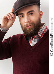 Portrait of confidence. Portrait of handsome young man adjusting his hat and looking at camera while standing against grey background