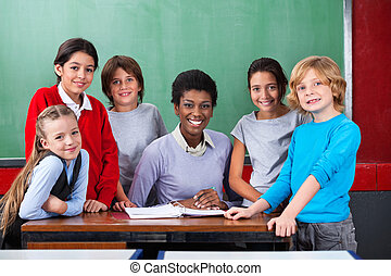 Portrait of confident African American female teacher and schoolchildren smiling together at desk in classroom